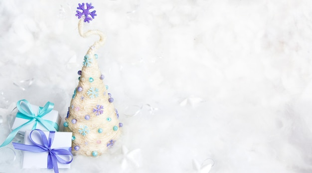 Decoratieve kerstboom en geschenken op een besneeuwde achtergrond. kopieer ruimte. blanco voor gefeliciteerd met de wintervakantie