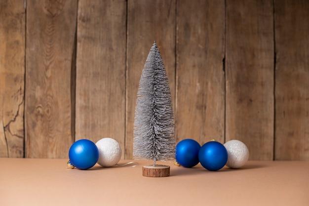 Decoratieve kerstboom en kerstboomversieringen op houten ondergrond.