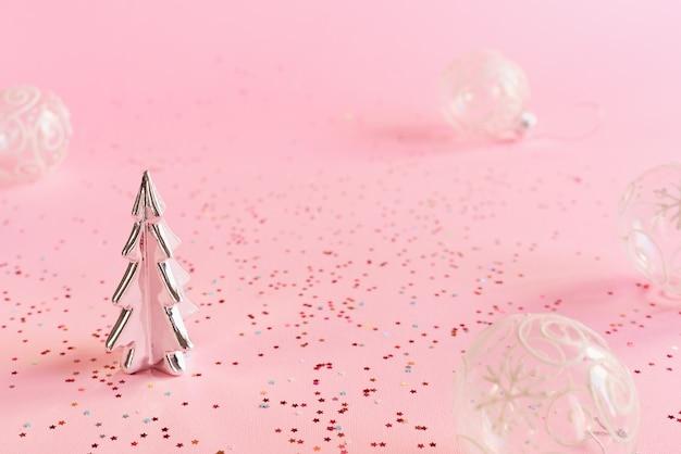 Decoratieve kerstboom en transparante ballen op roze achtergrond met kleurrijke confetti