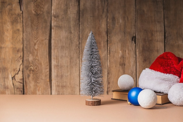 Decoratieve kerstboom, kerstversiering en kerstman hoed op een houten achtergrond.