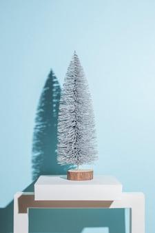 Decoratieve kerstboom op een blauwe achtergrond. harde schaduwen.