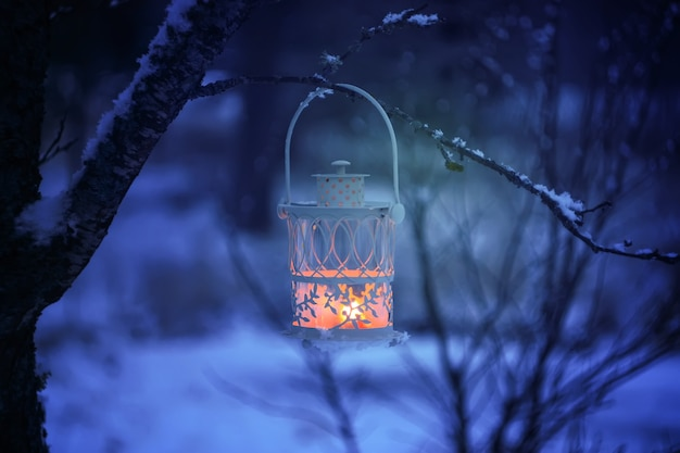 Decoratieve kerstlantaarn met brandende kaars die op een met sneeuw bedekte dennenboomtak hangt in een winterpark. nieuwjaar feestelijke kaart, poster, briefkaart ontwerp.