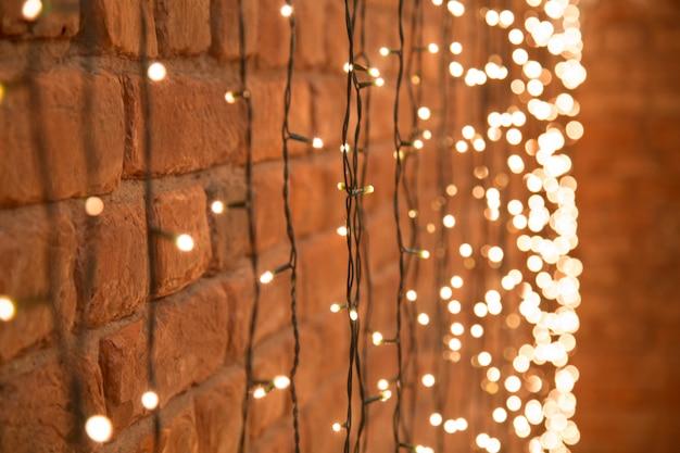 Decoratieve kerstmisslinger met lantaarns die op de baksteen hangen