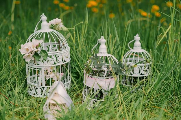 Decoratieve kooien met takken van een bloeiende appelboom in het decor van een bruiloft of een romantisch diner