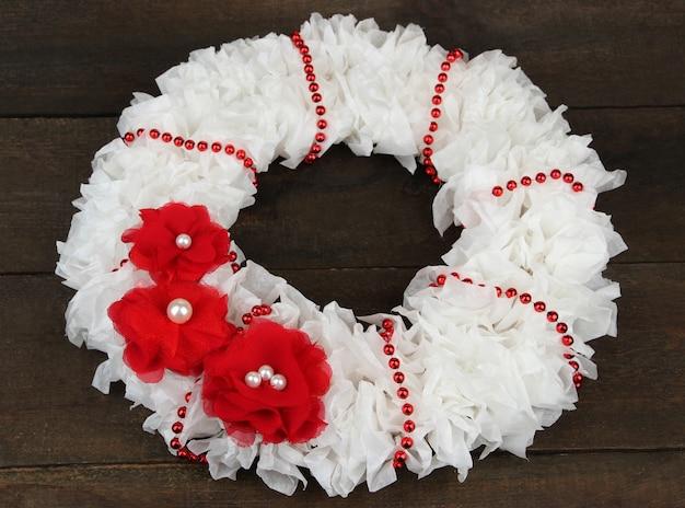 Decoratieve krans met bloemen op houten ondergrond