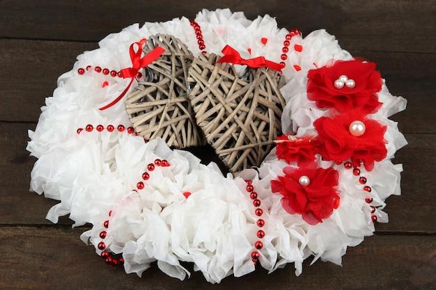 Decoratieve krans met rieten harten op houten achtergrond