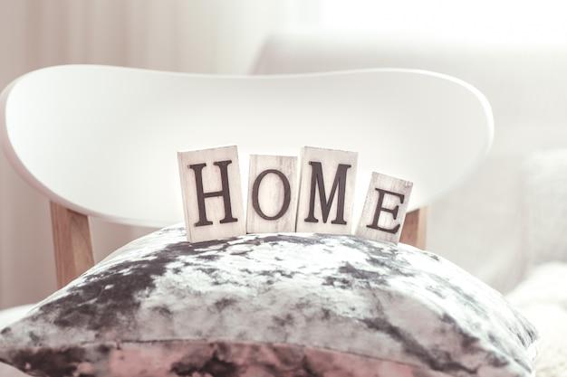 Decoratieve kussens en huis belettering op witte houten stijlvolle stoel. bank en rieten mand met kussens in de muur