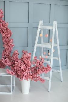 Decoratieve ladder met takken sakura witte houten ladder en slinger van eieren Premium Foto