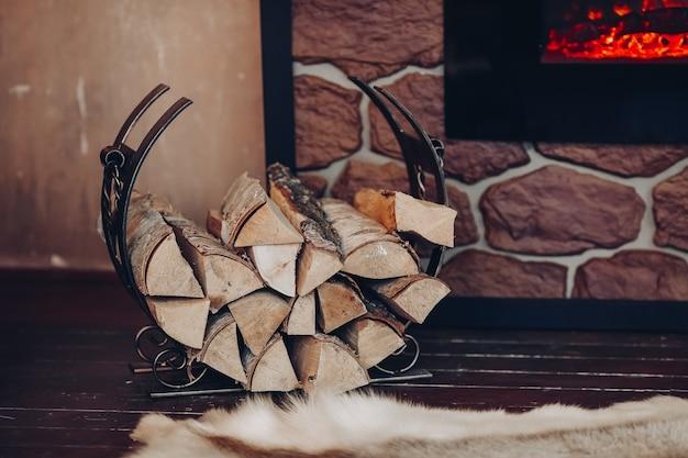 Decoratieve metalen houder met stapel houtblokken naast steenachtige open haard met brandende houtblokken.