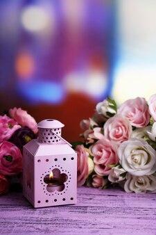 Decoratieve metalen lantaarn en kunstbloemen op lichte achtergrond
