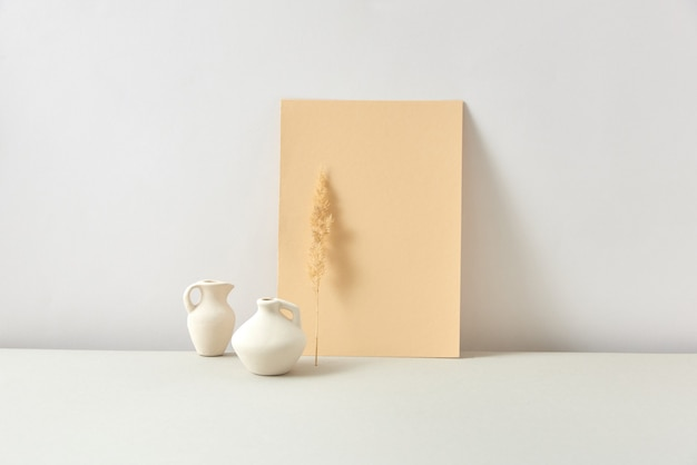 Decoratieve moderne compositie van handgemaakte witte keramische vazen met droge natuurlijke bloementakjes en verticaal staande papieren kaartrottekst op een lichtgrijze achtergrond, kopieerruimte. natuurlijk eco-concept.