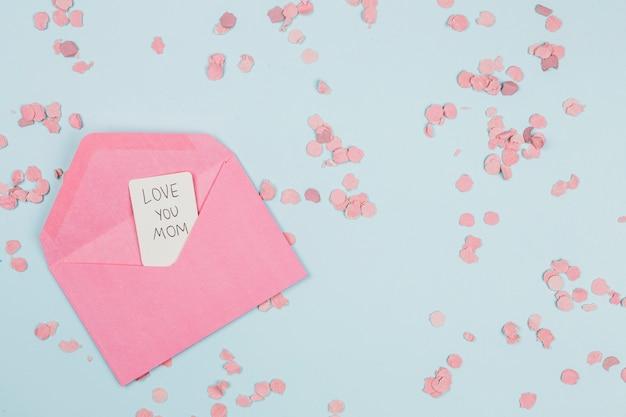 Decoratieve papieren confetti in de buurt van envelop met tag met woorden