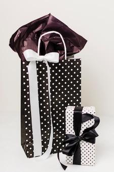 Decoratieve papieren zak en mooie geschenkdoos tegen witte achtergrond