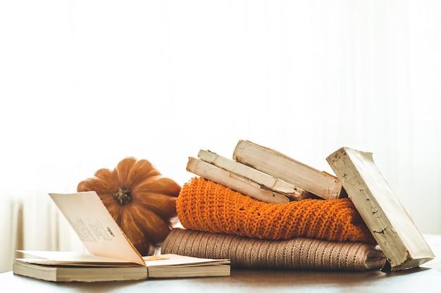 Decoratieve pompoen, gedroogde bloemen, boeken, warme truien. lezen in de herfstdag. herfstboeken. herfst lezen. gezellige sfeer.