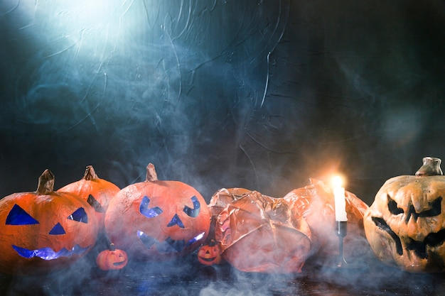 Decoratieve pompoenen in halloween-stijl en brandende kaars en rook