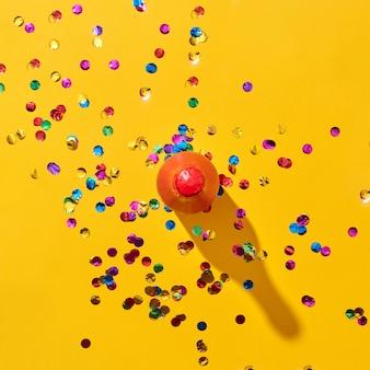 Decoratieve rood geschilderde fles wijn met harde schaduwen en kleurrijke confetti op een gele achtergrond, kopieer ruimte. bovenaanzicht. vakantie wenskaart