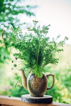Decoratieve samenstelling van weidebloemen in ceramische vaas op het terras van landhuis, close-up. boeket van wilde bloemen