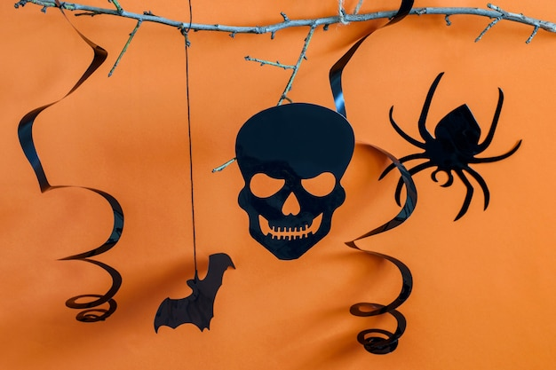 Decoratieve scull spider vleermuis dier en spinnenweb op de oranje halloween-achtergrond