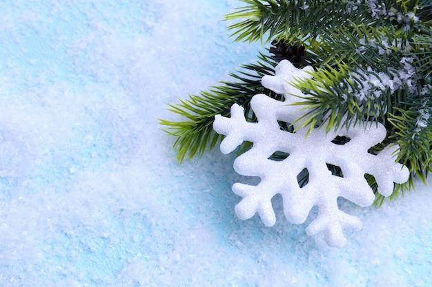 Decoratieve sneeuwvlok en dennenboom op lichte achtergrond