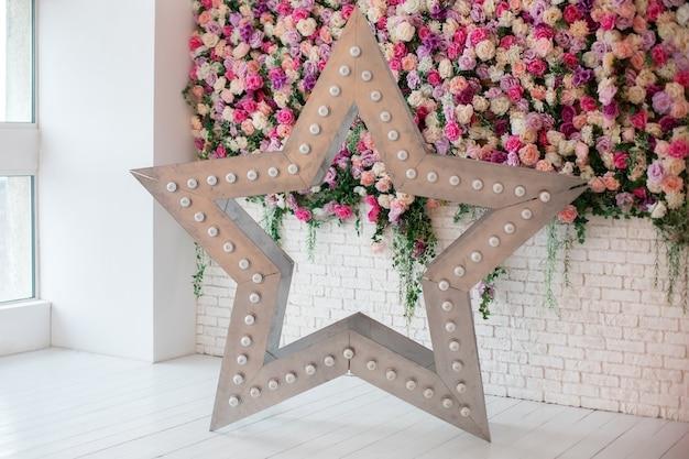Decoratieve ster met gloeiende led-retro gloeilampen. grote ster met bollen dichtbij muur met bloemen. stervormige witte led-verlichting lamp enkel frame. bruiloft decoratie. moderne huisbinnenhuisarchitectuur.