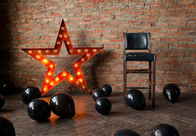 Decoratieve ster met lampen en zwarte ballonnen op de vloer.