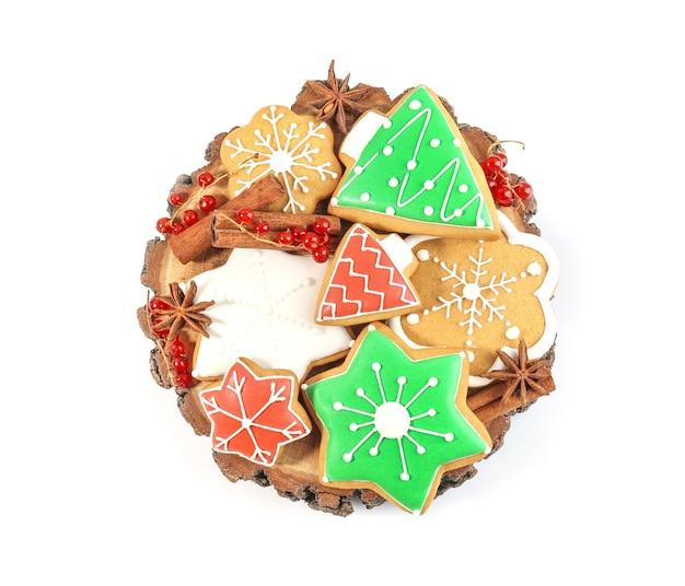 Decoratieve stomp met smakelijke kerstkoekjes op witte achtergrond