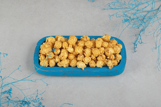 Decoratieve takken aan weerszijden van een kleine schaal met karamelpopcorn op marmer.
