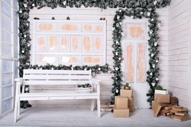 Decoratieve veranda met kerstversiering in witte tinten met slinger