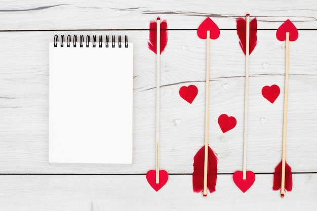 Decoratieve veren op toverstokken met kleine harten dichtbij notitieboekje