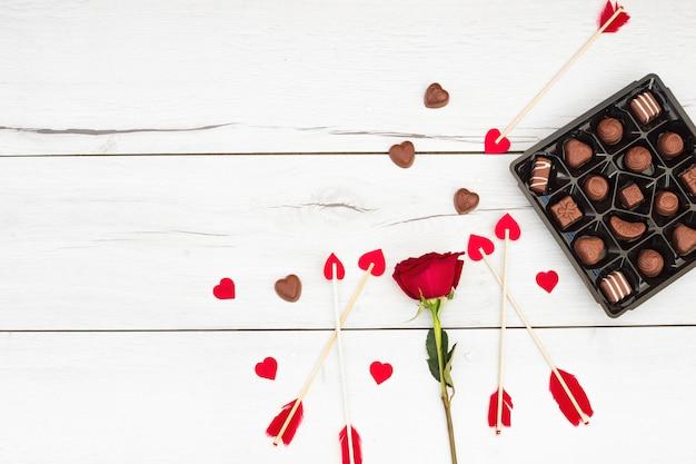 Decoratieve veren op toverstokken met kleine harten in de buurt van bloemen en snoep
