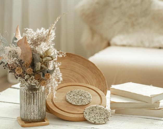 Decoratieve voorwerpen in het gezellige interieur van de kamer, een vaas met gedroogde bloemen op lichte houten tafel.
