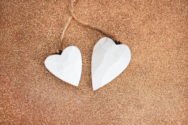 Decoratieve witte houten harten op bruin glitterbureau.
