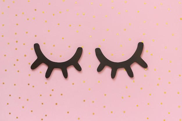 Decoratieve zwarte houten wimpers, gesloten ogen en gouden sterren op roze achtergrond.