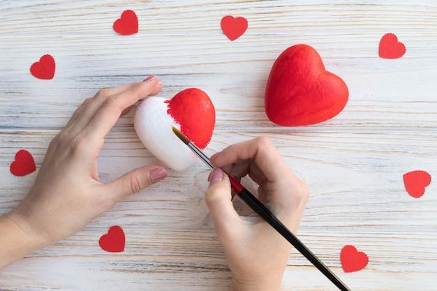 Decoreert handgemaakte harten met rode verf, doe-het-zelf valentijn.