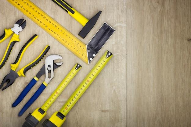 Decoreren en huis renovatie tools en accessoires op houten achtergrond. bovenaanzicht op gereedschappen.