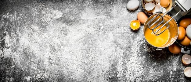 Deeg achtergrond. bereiding van het deeg. kloppen van verse eieren in de emmer-mixer op rustieke tafel.