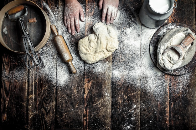 Deeg achtergrond. bereiding van het deeg met de ingrediënten. op de houten tafel.