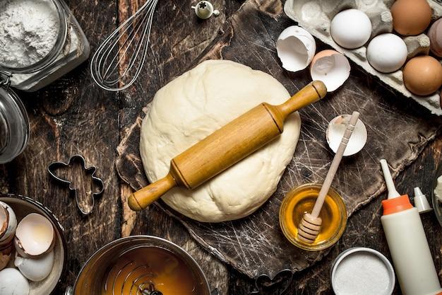 Deeg achtergrond. vers deeg met verschillende ingrediënten op een houten tafel.