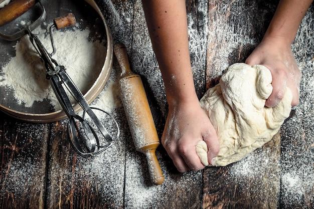 Deeg achtergrond. voorbereiding van deeg met gereedschap. op een houten tafel.