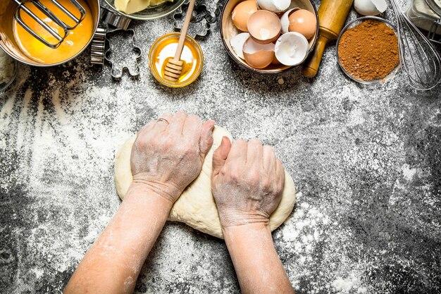 Deeg achtergrond. vrouw kneedt deeg met verschillende ingrediënten op tafel. op rustieke achtergrond.