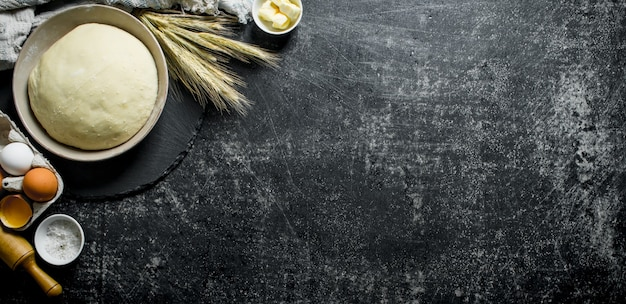 Deeg en ingrediënten om het deeg te bereiden. op donkere rustieke achtergrond
