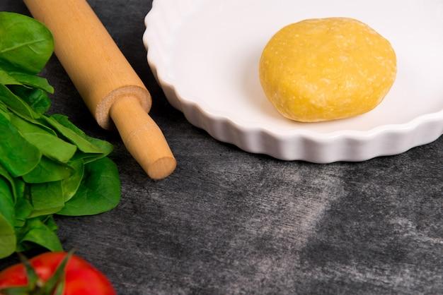 Deeg, groenen en tomaat op grijze houten tafel