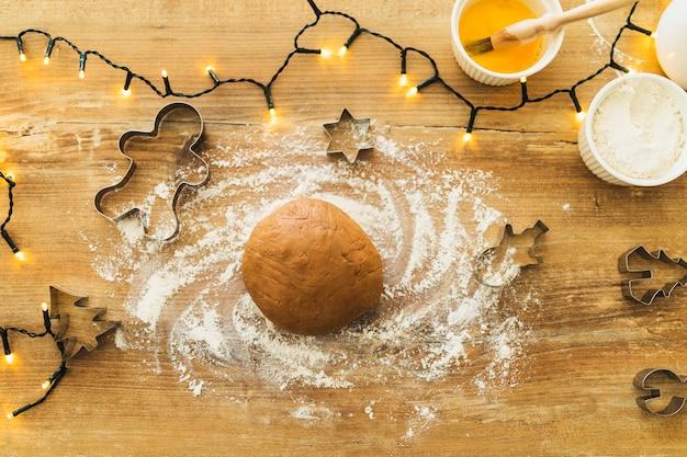 Deeg in de buurt van vormen voor koekjes en kerstverlichting