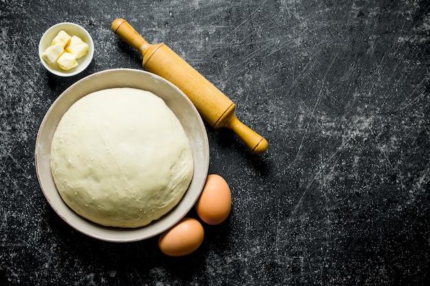 Deeg in een kom met eieren, deegroller en boter. op donkere rustieke achtergrond