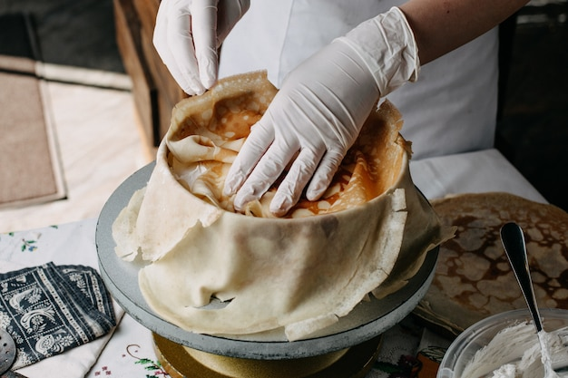 Deeg in ronde pan met kok spreiden plakjes op in de keuken