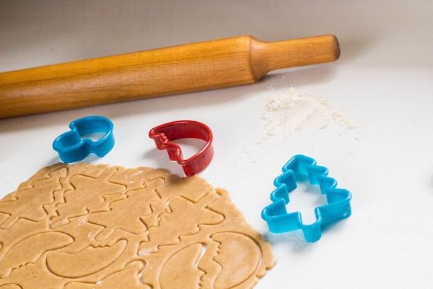 Deeg maken voor het bakken van peperkoekkoekjes in de vorm van sterren, boom, beer, maand en deegroller
