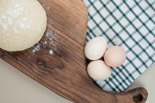Deeg met drie kippen verse witte eieren op houten snijplank.