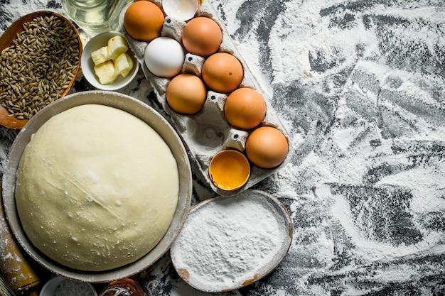 Deeg met eieren, boter en graan in kommen. op rustiek