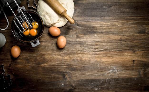 Deeg met verschillende ingrediënten. op een houten tafel.