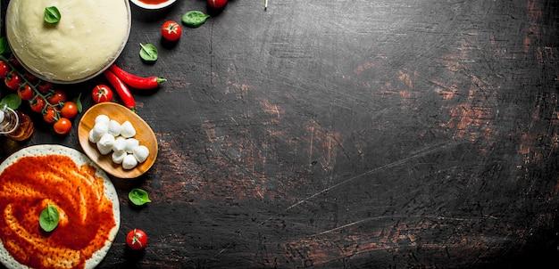 Deeg met verschillende ingrediënten voor zelfgemaakte pizza op donkere rustieke tafel